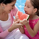 Close_up of a girl eating a slice of watermelon with her mother laughing