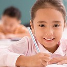 Portrait of a schoolgirl writing on a notebook with a pencil and smiling