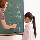Side profile of a female teacher teaching a schoolgirl on a blackboard