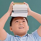 Close_up of a schoolboy holding books on his head