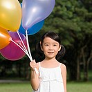 Close_up of a girl holding balloons and smiling