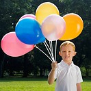Portrait of a boy holding balloons and smiling (thumbnail)