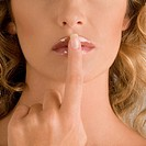 Close_up of a young woman with her finger on her lips