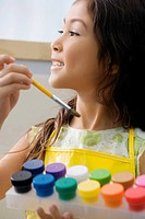 Close_up of a schoolgirl holding a paintbrush and a paint tray with watercolor paints