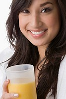 Portrait of a young woman holding a glass of orange juice and smiling