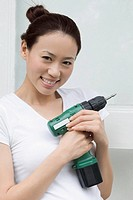Portrait of a young woman holding a drill and smiling