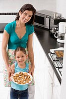 Young woman with her daughter holding a plate of cookies in the kitchen