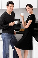 Portrait of a young couple holding their coffee cups in the kitchen and smiling