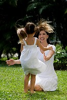 Young woman playing with her daughter in a park