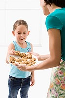 Close_up of a young woman serving cookies to her daughter