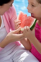 Close_up of a girl eating a slice of watermelon