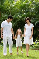 Young couple walking with their daughter in a garden