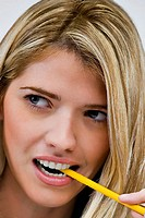 Close_up of a young woman biting a pencil
