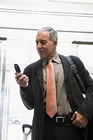 Businessman using a mobile phone in the waiting room of an airport