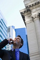 Low angle view of a businessman talking on a mobile phone and laughing