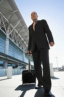 Low angle view of a businessman pulling his luggage outside an airport