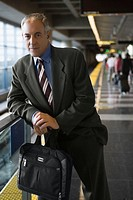 Portrait of a businessman holding a bag and standing at a subway station