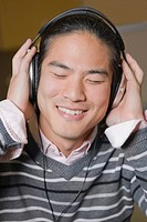 Close_up of a young man listening to music and smiling