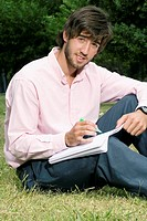 Portrait of a young man writing with a pen on a notepad