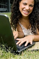 Portrait of a teenage girl working on a laptop and smiling