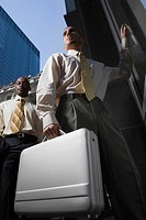 Low angle view of a businessman holding a briefcase and another businessman standing behind him