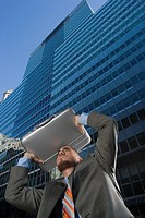 Low angle view of a businessman using his briefcase as a shade