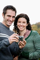 Portrait of a couple holding a digital camera and smiling