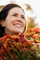 Close_up of a mature woman holding bunch of flowers and smiling