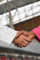 Close_up of two businesswomen shaking hands at an airport