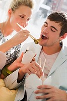 Young woman feeding food to a young man (thumbnail)