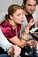 Portrait of a young woman eating cake and sitting with her friends