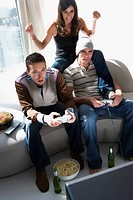 Two young men and a young woman playing video game