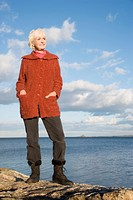 Senior woman standing on a rock at seaside