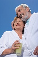 Low angle view of a senior couple standing together with a glass of juice