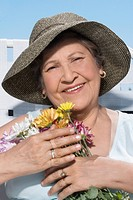 Close_up of a senior woman holding a bunch of flowers and smiling