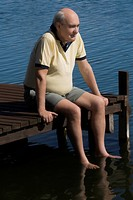Senior man sitting on a boardwalk