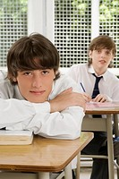 Portrait of a young man leaning on a desk with a teenage boy sitting behind him in a classroom (thumbnail)