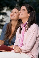 Side profile of two mid adult women sitting together and smiling (thumbnail)