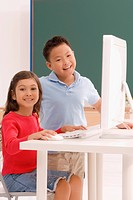 Portrait of a schoolboy and a schoolgirl using a computer in a classroom