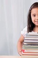 Portrait of a schoolgirl smiling with a stack of books in front of her