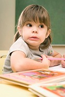 Close_up of a girl sitting at a desk and holding a colored pencil