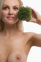 Close_up of a young woman holding wheatgrass and smiling