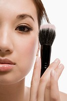 Close_up of a young woman holding a make_up brush
