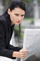 Close_up of a businesswoman reading a newspaper