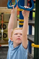 High angle view of a boy hanging on monkey bars