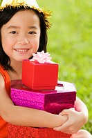 Portrait of a girl holding a stack of birthday gifts and smiling