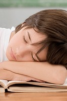 Close_up of a schoolboy sleeping on a desk in a classroom