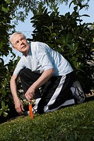 Senior man kneeling in a garden and holding a gardening fork