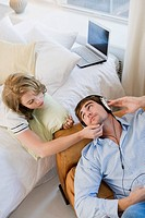 High angle view of a young man listening to music and a young woman lying on the bed beside him (thumbnail)