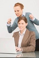 Businesswoman working on a laptop with her colleague clenching teeth behind her (thumbnail)